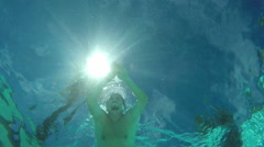 Man swims view from under the water, the sun's rays Stock Footage