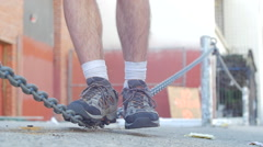 Man working out in the city balances on chain rope, slow motion. Stock Footage