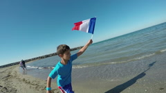 Boy  running along the beach with the flag of France in the hands of Stock Footage