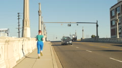 A young woman running in an urban environment, slow motion. Arkistovideo