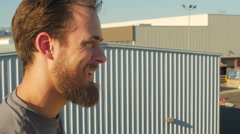 A young man with a beard drinking water and working out in urban environment, sl Stock Footage