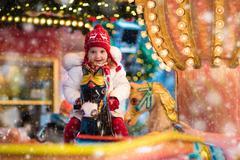 Child riding carousel on Christmas market Stock Photos