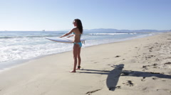 A young woman surfer standing on the beach holding her surfboard as she looks ou Stock Footage