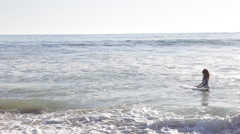 A young woman surfer walking out into the ocean to catch some waves. Stock Footage