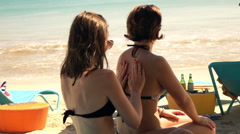 Woman applying sunscreen on arms and back her friend on the beach, super slow mo Stock Footage