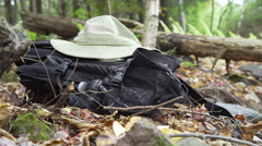 A hiker setting his hiking stick down next to backpack and hat. Stock Footage