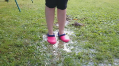 Female feet in rubber boots jumping in puddle. Slow-motion video Stock Footage