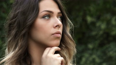 Beautiful woman waiting for someone in the park: closeup portrait Stock Footage