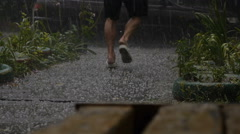 Man Running out of the Heavy Rain on Asphalt Road. Static Shoot Stock Footage