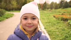 Portrait Adorable Little Girl in jacket and hat Smiles outdoor Stock Footage