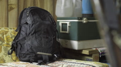 A older hiker grabbing backpack from inside a cabin in the woods. Stock Footage