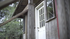 An older man leaving his cabin in the woods to go on a hike. Stock Footage