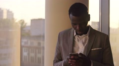 Young black man in suit chating on the phone and smiling standing by window in Stock Footage