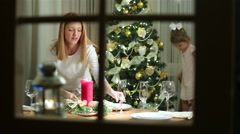 Young mother server festive table, her little daughter decorates Christmas tree. Stock Footage