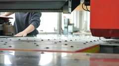 Punching little holes in stainless steel with a heavy machine in a factory, 4K Stock Footage