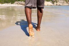 Man walking with bare feet on the beach Stock Photos