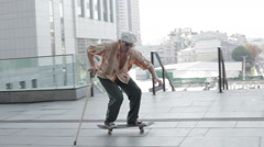Old man on a skateboard. Stock Footage
