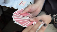 Woman draws a card game which is then placed on the table 3c Stock Footage