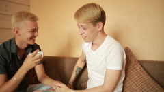 Happy gay couple having breakfast on the couch. LGBT Stock Footage