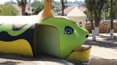 Green face of a huge play centipede in children's play park in Israel Stock Footage