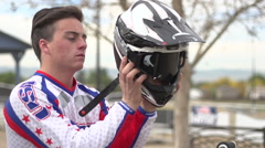 A young man bmx rider sitting on bike while putting on helmet , super slow moti Stock Footage