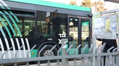 Orthodox jews walking by a large green and black bus Stock Footage