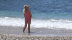 Blonde girl in a swimsuit playing on the seashore with a stick that hits wate Stock Footage