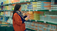 Woman in red coat shopping in supermarket Stock Footage
