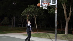 A young business man playing basketball in his suit after work on an outdoor cou Stock Footage