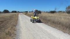 Motorcyclist driving a quad on a dirt road outside the town bordered by dried Stock Footage
