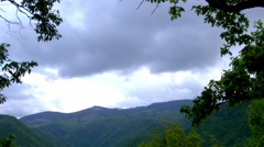 Panorama over mountains covered by forests deep and dark in a day with rain Stock Footage