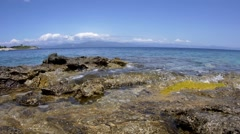 Waves that burst of rocky shore and in the distance you can see mountains cov Stock Footage