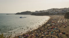 Crowded beach at sunset in the beautiful coastal town of Albufeira, Portugal. 4K Stock Footage