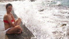 Girl sits on concrete pier and observes the waves. Stock Footage