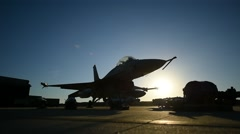 Silhouette of an F16 Fighting Falcon aircraft on the runway at sunset Stock Footage