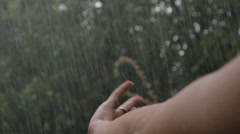 Hand reaches up to stormy sky, welcomes rain bouncing off fingertips Stock Footage