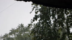 Drops of rain fall from the roof of the pavilion in hard storm outside Stock Footage