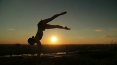 Woman doing Ashtanga yoga in the park at sunset Stock Footage