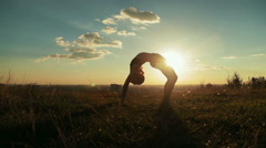 Woman practicing yoga in the park at sunset - drop back, wheel pose Stock Footage