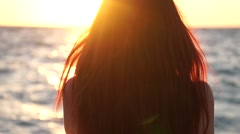 Young girl with long hair standing and watching at sunset Stock Footage