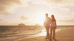 Romantic couple walking at beach at sunset embracing and holding hands Stock Footage