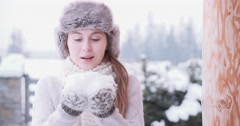 Woman Blowing Snow near Winter Mountain Cottage, SLOW MOTION  Stock Footage