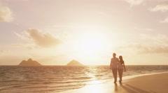 Beach sunset couple walking romantic on honeymoon on Hawaii Stock Footage