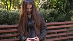 Beautiful woman with long hair uses cell smartphone outdoors in the park Stock Footage