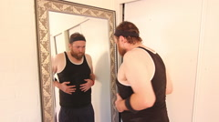 An out of shape man looking at himself in the mirror. Stock Footage