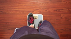 An out of shape man weighing himself on a scale. Stock Footage