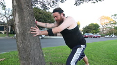 An out of shape man using a tree to stretch before working out. Stock Footage
