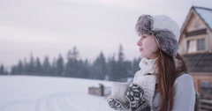 Woman with Cup of Hot Drink by the Cozy Cottage in Winter. 4K SLOW MOTION  Stock Footage