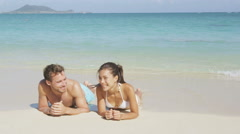 Honeymoon beach couple sun tanning relaxing on holiday travel Stock Footage