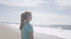 A woman runner resting on the beach after her run, slow motion. Stock Footage